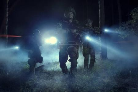 Special Forces soldiers in action. Elite squad moves through fog and smoke.