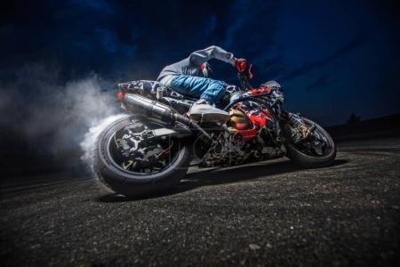 Photo pour Un motocycliste fait une cascade sur sa moto. Biker faire un cascade difficile et dangereux . - image libre de droit