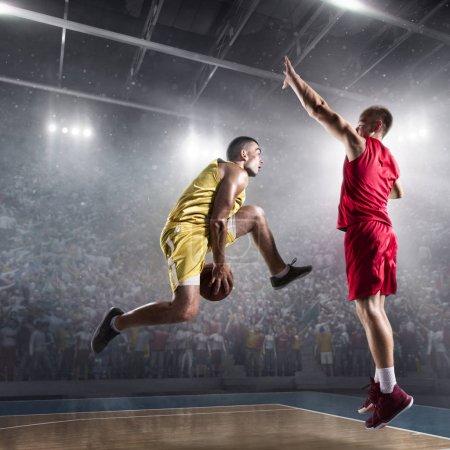 Basketball players on big professional arena makes slam dunk