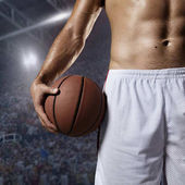 Basketball player hold a ball on professional arena