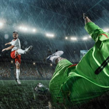 Soccer players performs an action play on a professional rainy stadium