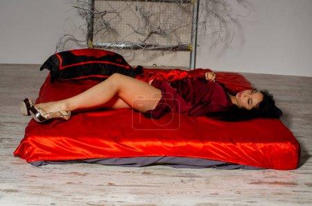 Photo pour Sexy, séduisante et belle jeune femme avec un corps mince et chaud et la peau tannée se pose dans les sous-vêtements érotiques en laiton noir dans le studio sur les feuilles blanches, fond sombre. Fillette dans la lingerie - image libre de droit