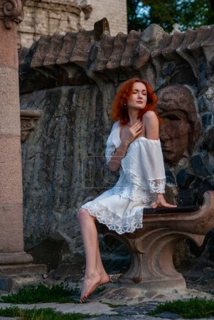 Photo for Beautiful redhead woman in white summer dress posing outdoor - Royalty Free Image