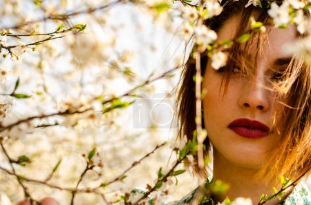 Photo for Beautiful attractive woman posing near flowering tree at sunny day - Royalty Free Image