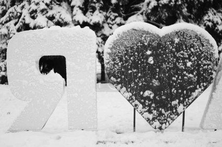 Photo pour L'inscription amour dans la neige, et une empreinte de coeur - image libre de droit