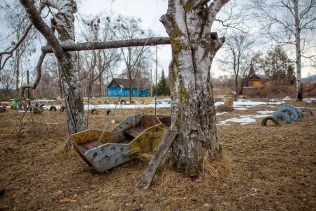 Russian village. Old wooden children's swing on a ...