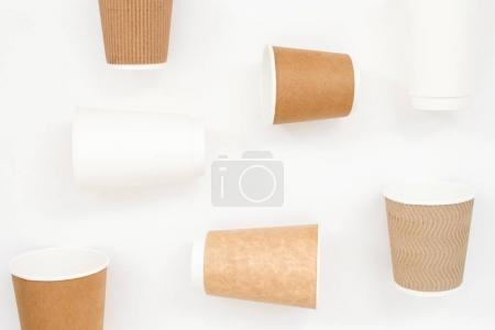 Photo pour Gobelets en papier jetables sur fond blanc. Composition de la géométrie, vue de dessus. - image libre de droit