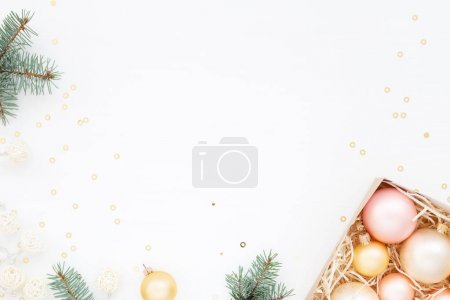 Photo for Christmas lights and ornaments on white. New Year balls in a box, fir, gold confetti. Winter holidays preparations. Top view. Minimal festive card. - Royalty Free Image