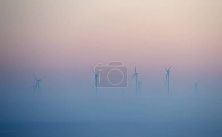 wind turbines on field in foggy morning