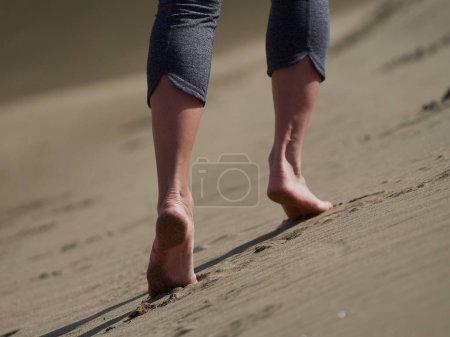 Photo pour Pieds nus de la jeune femme jogging/marche sur la plage au lever du soleil - image libre de droit