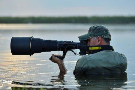 wildlife photographer standing in the water