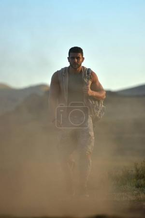 athletic young man in dusty field