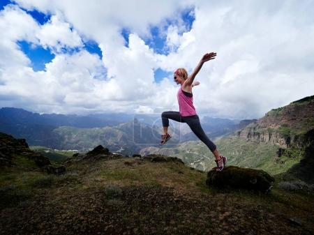 woman jumping on top of mountain
