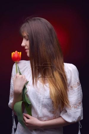 pretty woman holding red tulip