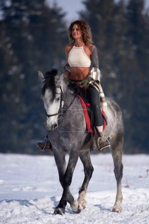 woman riding horse outdoor in winter