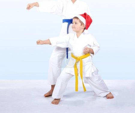 Kids in karategi are beating punch arm