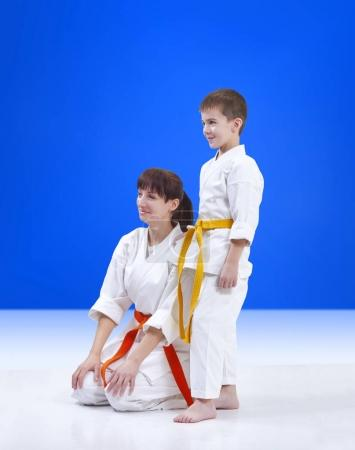 Family athletes in karategi on a blue background