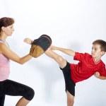 Постер, плакат: Boy is beating kick leg on the simulator that mom keeps