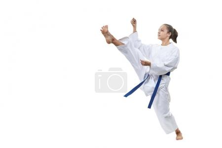 On a white background the girl with a blue belt beats kick