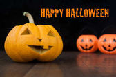 Halloween still life with pumpkins on wooden floor and dark background with Happy halloween text