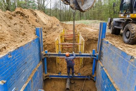 Installation of metal supports to protect the walls of the trench.