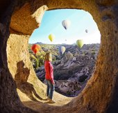 Woman watching  like colorful hot air balloons flying over the valley at Cappadocia