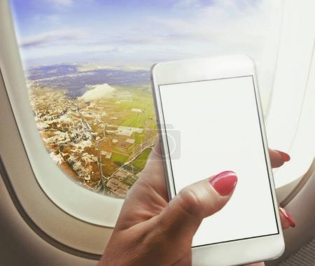 Photo pour Voyageuse assise près de la fenêtre et de l'aile, tenant un téléphone intelligent travaillant à bord d'un avion, écran vide vide.Concept art - image libre de droit