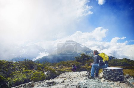 Rear view of a man sitting on a stone and looking at mountains and glacier.