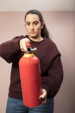 Young woman pointing a fire extinguisher forwards