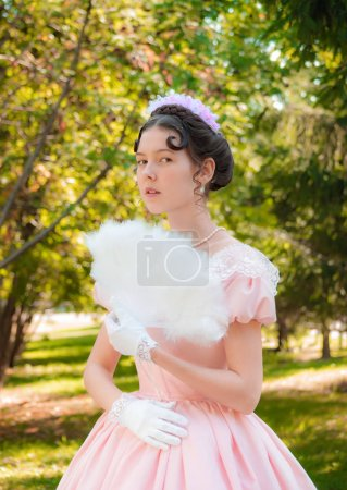 Romantic, charming girl fanning herself fan and with an attentiv