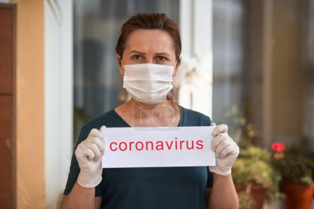 Photo for Woman in medical mask holding card with coronavirus lettering. Covid-19. - Royalty Free Image
