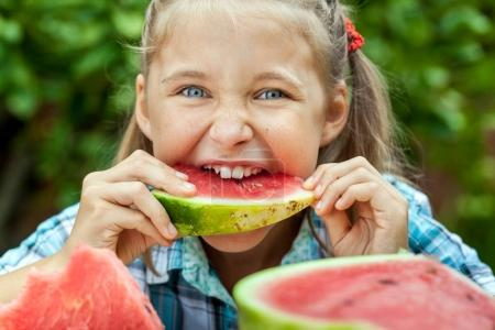 Young girl eating ripe watermelon