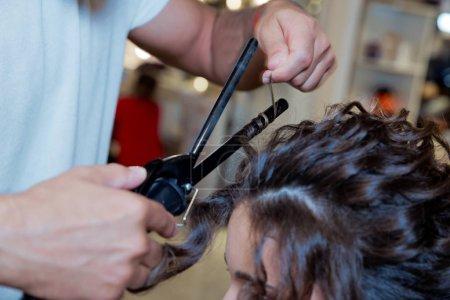 Photo pour Gros plan de la main du styliste en utilisant du fer à friser pour les cheveux des clientes. coiffeur redresser les cheveux plus. blonde faisant les fers à friser dans le salon de beauté. Coiffeur professionnel  . - image libre de droit