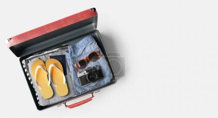 Red open travel bag with clothes on white background