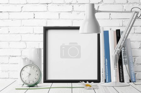 empty photo frame with pile of books and alarm clock with table lamp