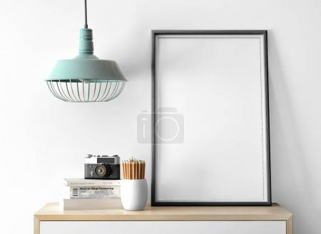 empty photo frame with camera on pile of books and pencils on table