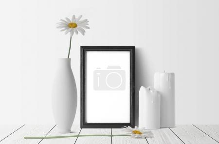 empty photo frame with white candles and chamomiles with vase