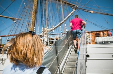 People climbing stairs on ship board, back view