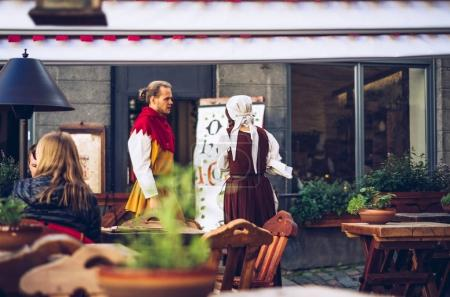 Workers of street cafe wearing authentic estonian clothing talking to each other, Estonia