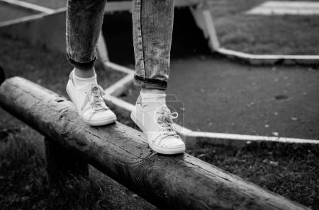 Legs in sneakers walking on wooden log