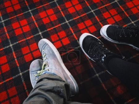feet in sneakers on red plaid