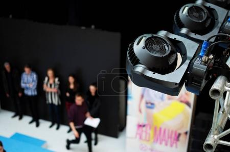 projector illuminating stage with people