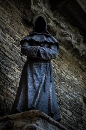 old monk statue wearing robe