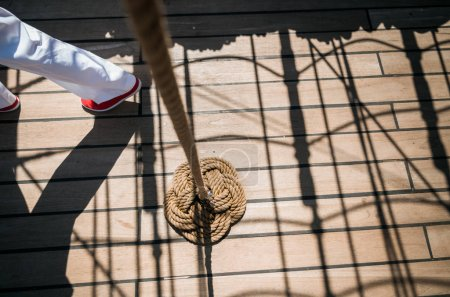 Sailboat deck, knot of rope and sailor