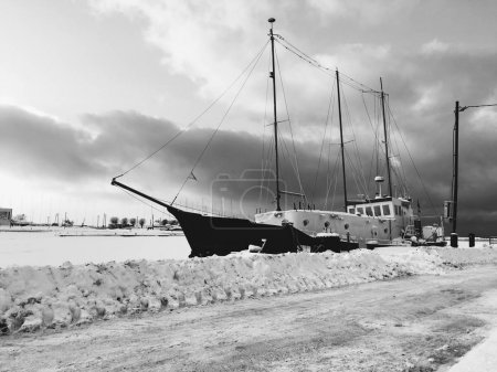 Vintage nautical vessel moored in harbor, black and white