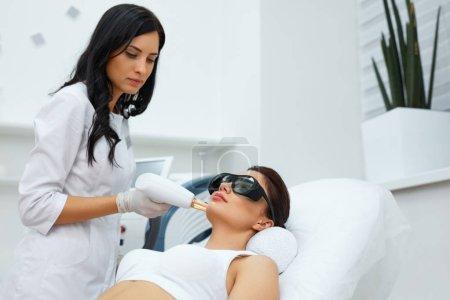 Photo pour Procédure beauté. Gros plan de l'esthéticienne utilisant la thérapie laser pour rajeunir la peau du visage. Belle visage de femme en bonne santé Obtenir la peau Resurfaçage dans le salon de spa. Traitement du corps. Haute résolution - image libre de droit