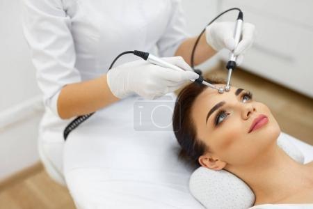 Photo pour La peau du visage. Gros plan de belle femme recevant un traitement de micro-courant facial du thérapeute au salon de spa. Esthéticienne utilisant des impulsions électriques pour les procédures faciales. La cosmétologie. Haute résolution - image libre de droit