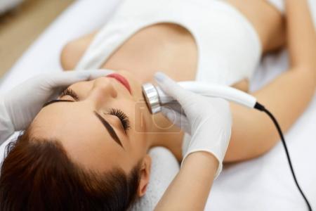 Photo pour La cosmétologie. Belle femme recevant une cavitation par ultrasons de la peau du visage. Gros plan de visage féminin recevant des cosmétiques anti-âge à l'aide d'une machine de cavitation à ultrasons. Soins du corps. Haute résolution - image libre de droit