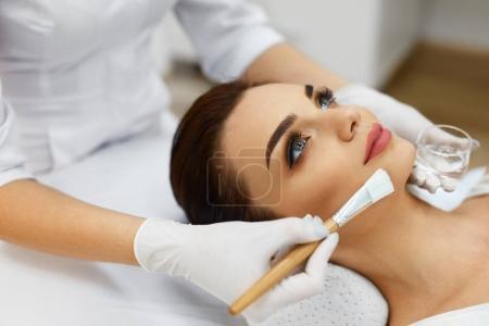 Photo pour Soins de la peau. Esthéticienne Appliquer un masque à huile de beauté sur le visage en utilisant le pinceau dans le salon de spa. Gros plan de la cliente obtenant une procédure hydratante dans une clinique de beauté. La cosmétologie. Haute résolution - image libre de droit