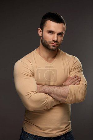Photo for Handsome Man Portrait. Closeup Of Strong Sexy Young Male With Beautiful Face, Fit Muscular Body Standing With HIs Arms Crossed. Attractive Confident Guy On Grey Background. High Resolution - Royalty Free Image